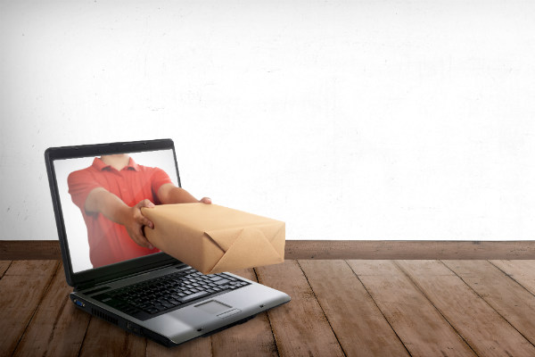 Man passing a package through a laptop screen