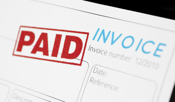 Close-up picture of an invoice with red paid stamp.