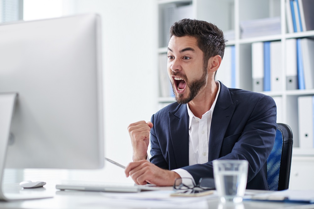 Happy young entrepreneur screaming of joy when looking at computer screen