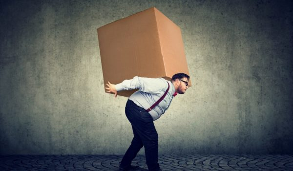 an delivering huge heavy box on back