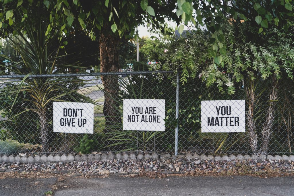 positive affirmation posters on a fence