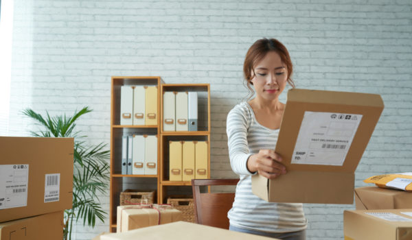 Young ethnic woman opening carton box while working in modern postal service of delivery