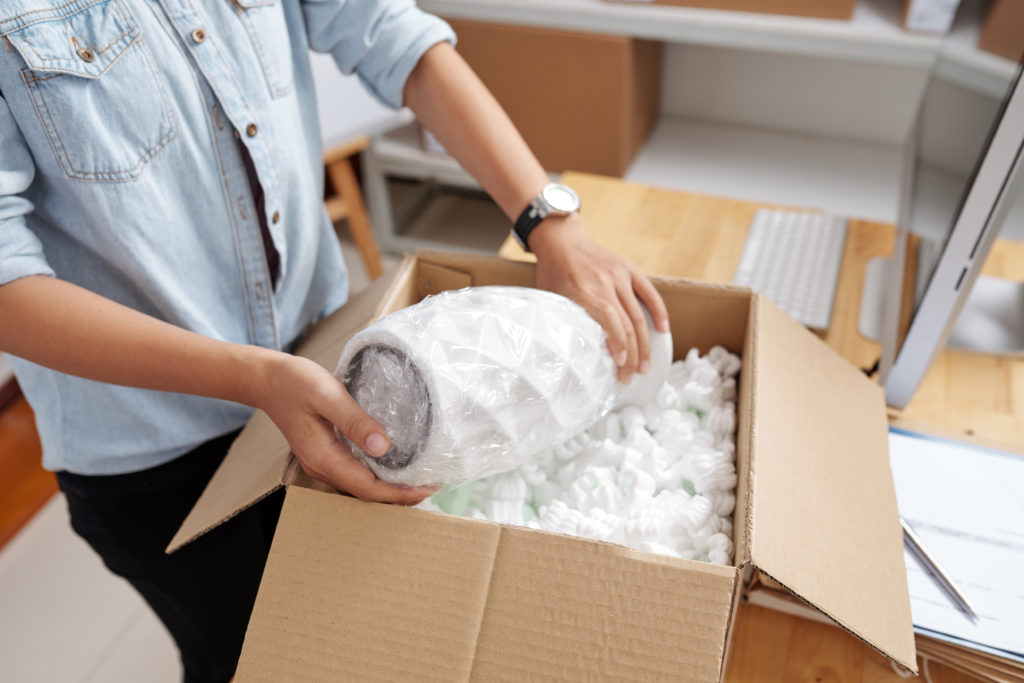 Post office worker packing vase in box for delivery